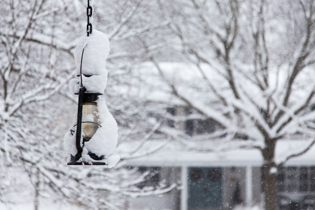 54978309 - a lantern hangs in the snowy yard in front of a residential suburban home. focus is on lantern, house is in background
